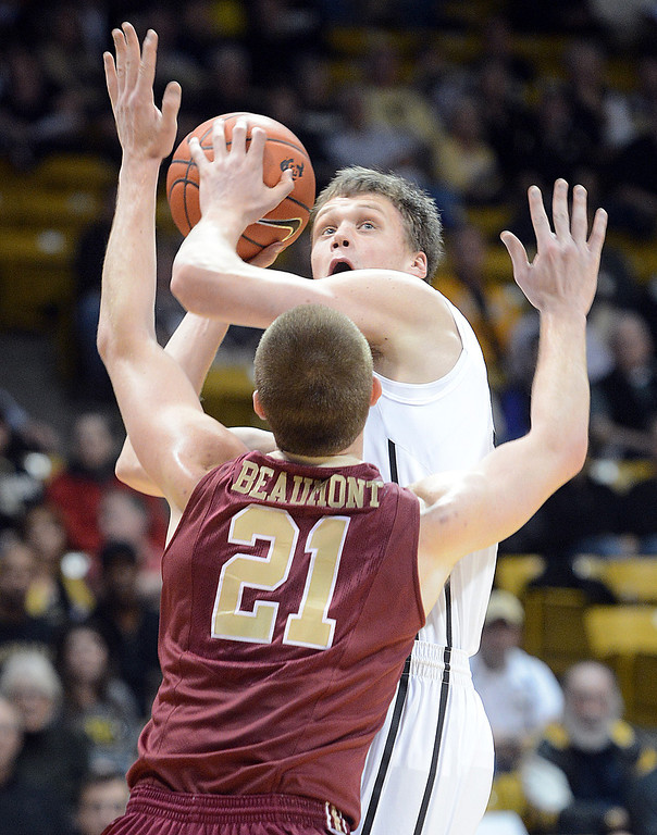 . Ben Mills of CU looks to score over Ryley Beaumot of Elon during the first half of the December 13, 2013 game in Boulder. (Cliff Grassmick/Boulder Daily Camera)