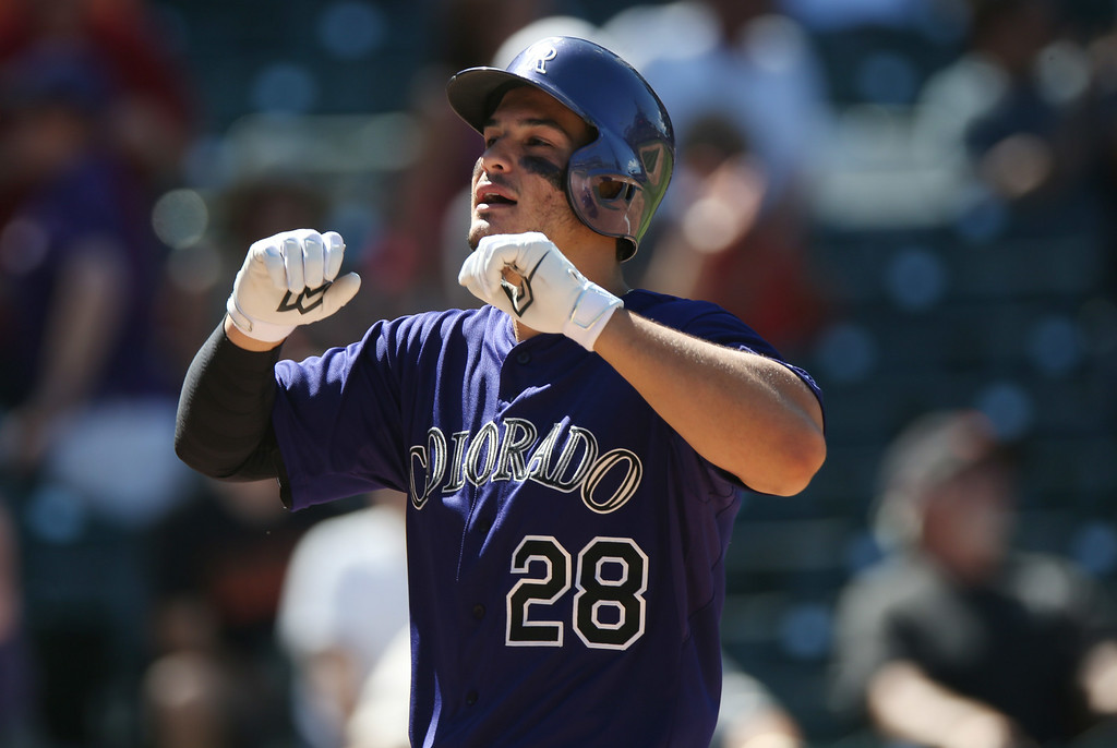 . Colorado Rockies\' Nolan Arenado celebrates his three-run home run as he crosses home plate against the San Francisco Giants in the fifth inning of the Rockies\' 9-2 victory in a baseball game in Denver on Wednesday, Sept. 3, 2014. (AP Photo/David Zalubowski)