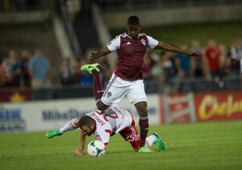 . DENVER - JULY 4: #9 Edson Buddle of the Colorado Rapids runs the ball over #25 Brandon Barklage of the New York Red Bulls during the second half of a MLS soccer match on July 4, 2013 at Dick\'s Sporting Goods Park. The Rapids defeated the Red Bulls 2-0.(Photo By Grant Hindsley / The Denver Post)