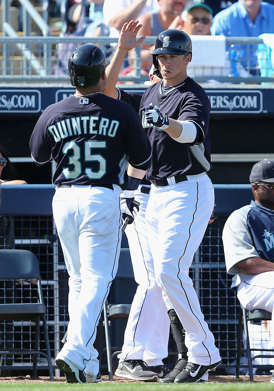 . Justin Smoak #17 of the Seattle Mariners high fives Humberto Quintero #35 after scoring a fifth inning run against the Colorado Rockies during the spring training game at Peoria Stadium on March 3, 2014 in Peoria, Arizona.  (Photo by Christian Petersen/Getty Images)