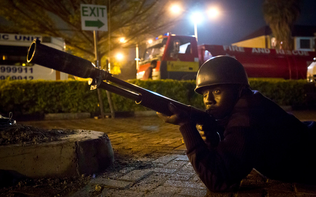 . An armed police officer takes cover during a bout of gunfire outside the Westgate Mall in Nairobi, Kenya Saturday, Sept. 21, 2013.  Gunmen threw grenades and opened fire Saturday killing at least 22 people in an attack targeting non-Muslims at an upscale mall in Kenya\'s capital that was hosting a children\'s day event, a Red Cross official and witnesses said. (AP Photo/Ben Curtis)