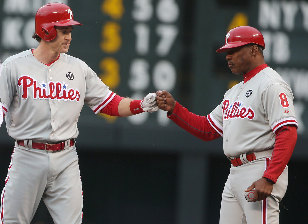 . Philadelphia Phillies\' Chase Utley, left, is congratulated after hitting a single against the Colorado Rockies by first base coach Juan Samuel in the first inning of a baseball game in Denver on Saturday, April 19, 2014. (AP Photo/David Zalubowski)