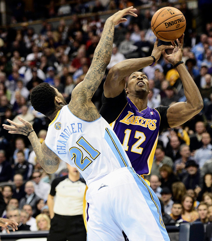 . Los Angeles Lakers\' Dwight Howard (R) looses control of the ball under pressure from Denver Nuggets\' Wilson Chandler during their NBA basketball game in Denver, Colorado February 25, 2013.   REUTERS/Mark Leffingwell  (UNITED STATES - Tags: SPORT BASKETBALL TPX IMAGES OF THE DAY)
