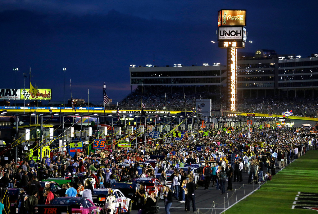 . Fans mill about on pit road before the NASCAR Sprint Cup Series auto race at Charlotte Motor Speedway in Concord, N.C., Saturday, Oct. 12, 2013. (AP Photo/Gerry Broome)