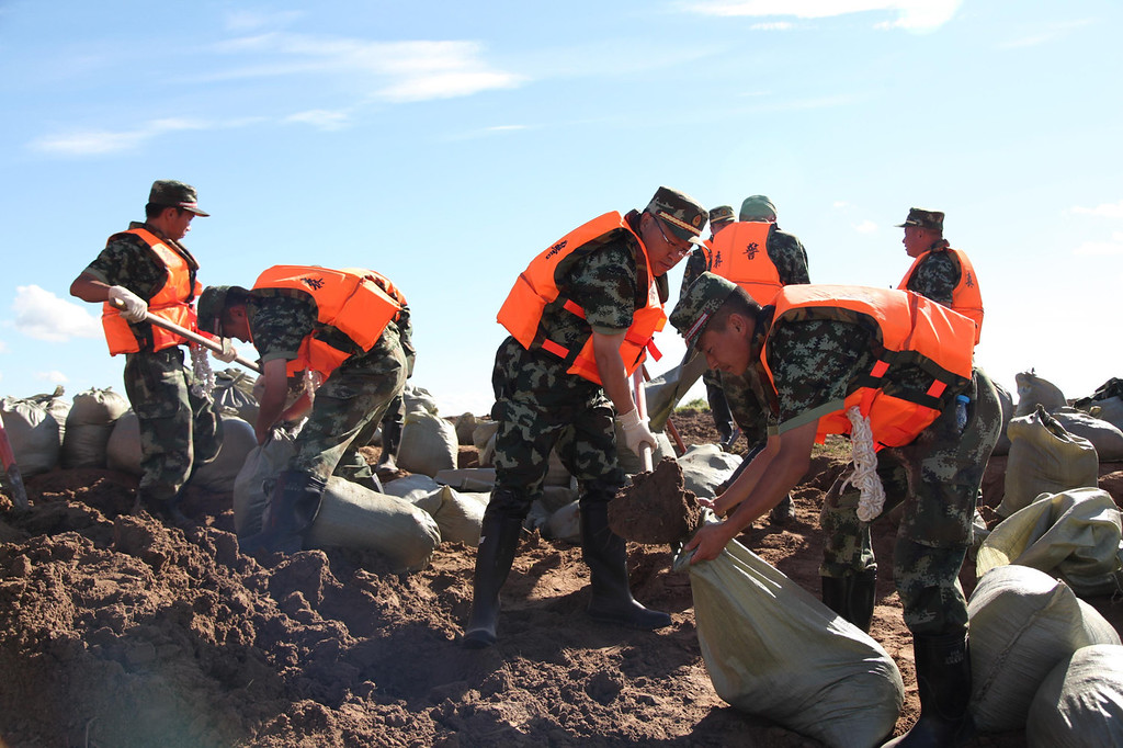 . Soldiers stack sandbags to strengthen a dam at the flooding Nenjiang river on August 18, 2013 in Daqing, China. 32 are missing and 15 are dead after a torrential rain hit Liaoning Province of China.  (Photo by ChinaFotoPress/ChinaFotoPress via Getty Images)