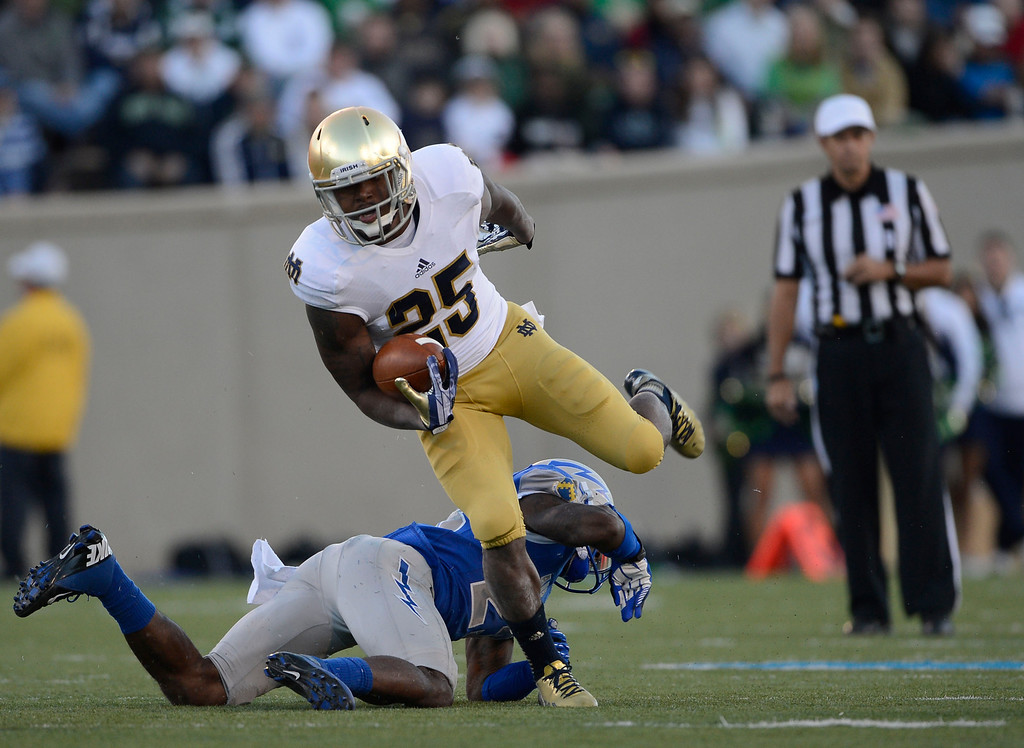 . COLORADO SPRINGS, CO - OCTOBER 26: Notre Dame RB, Tarean Folston, escapes from Air Force DB, Steffon Batts, in the third quarter at Falcon Stadium, Saturday afternoon, October 26, 2013. (Photo By Andy Cross/The Denver Post)