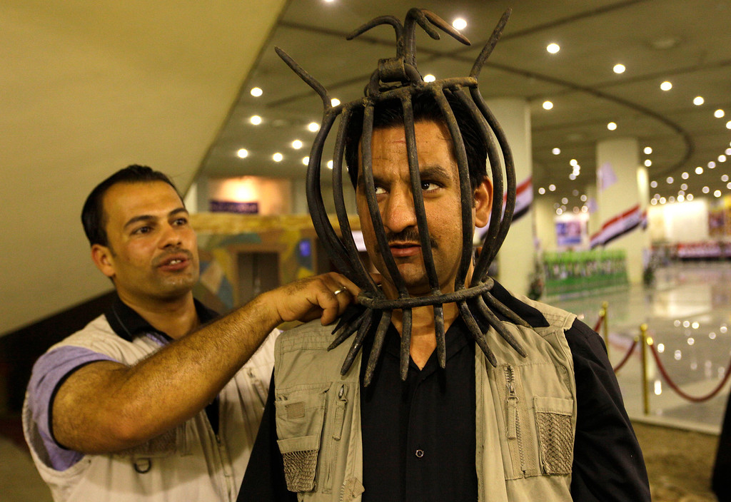 . An Iraqi man wears a torture device used by the regime of Iraq\'s ousted leader Saddam Hussein at the Shaheed Monument in Baghdad, Iraq, Friday, May 24, 2013. Saddam Hussein had the split teardrop-shaped sculpture built in the middle of a manmade lake in the early 1980s to commemorate Iraqis killed in the Iran-Iraq War. The names of hundreds of thousands of fallen Iraqi soldiers are inscribed in simple Arabic script around the base. In recent years, the Shiite-led government has begun turning it into a museum honoring the overwhelmingly Shiite and Kurdish victims of Saddam\'s Sunni-dominated but largely secular regime. (AP Photo/Khalid Mohammed)