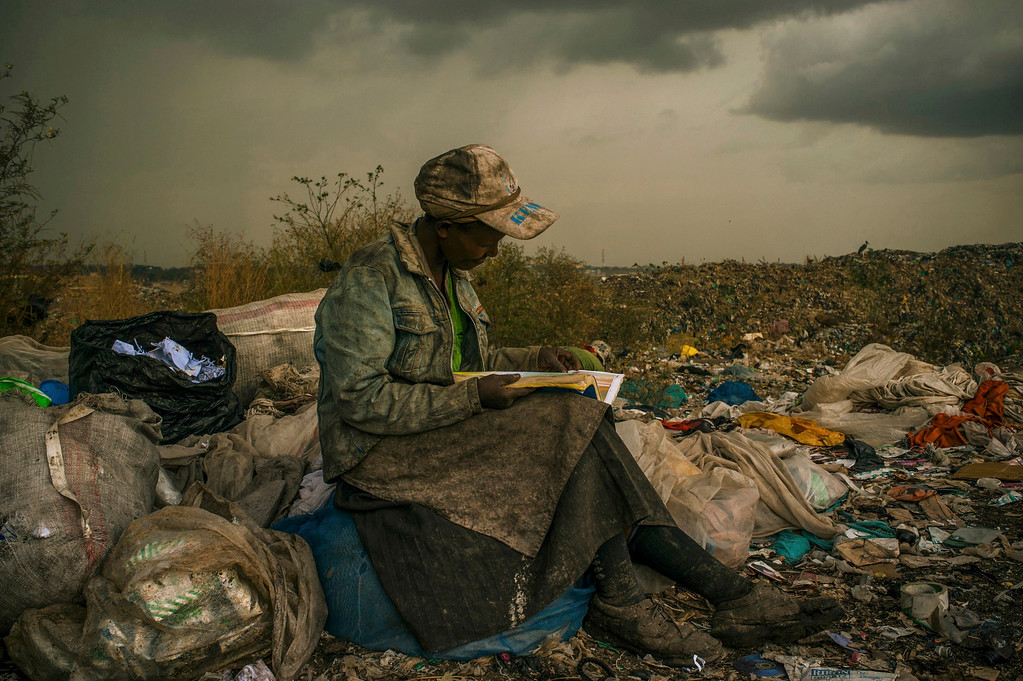. Micah Albert of the U.S., a photographer working for Redux Images, has won the first prize in the Contemporary Issues Single category of the World Press Photo Contest 2013 with this picture of a woman pausing in the rain as she works as a trash picker at a 30-acre dump in Nairobi,  taken on April 3, 2012 and distributed by the World Press Photo Foundation February 15, 2013.    REUTERS/Micah Albert/Redux Images/Handout