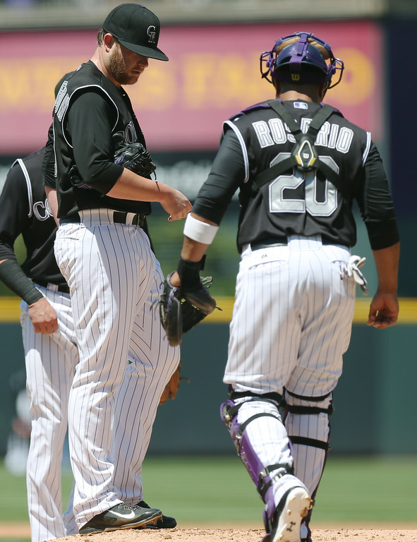 . Colorado Rockies starting pitcher Brett Anderson, left, confers with catcher Wilin Rosario after Anderson gave up a double to bring in two runs to Minnesota Twins\' Eduardo Escobar in the first inning of an interleague baseball game in Denver on Sunday, July 13, 2014. (AP Photo/David Zalubowski)