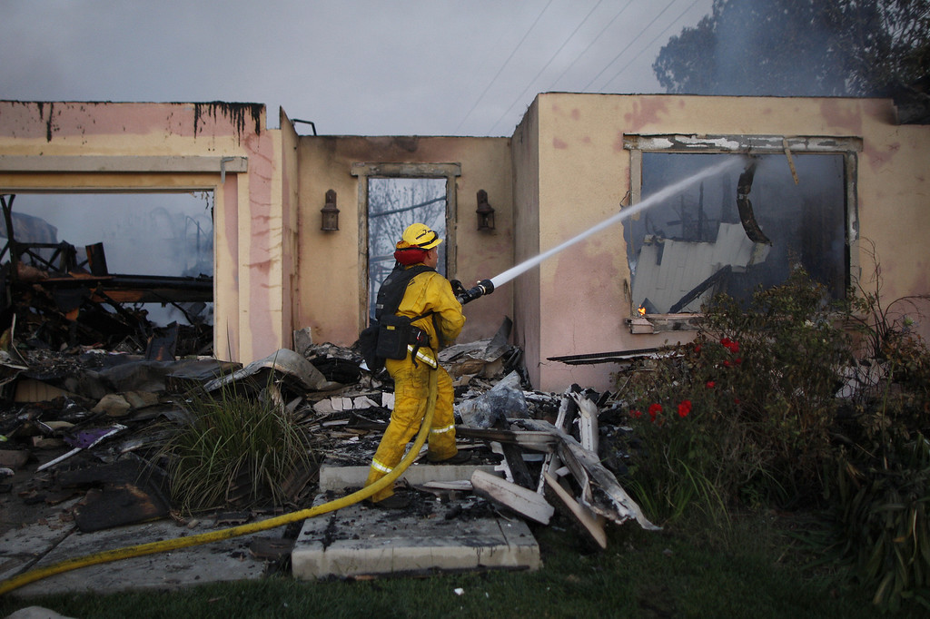 . A firefighter hoses down the smoldering ruins of a house that was destroyed in the Poinsettia fire, one of nine wildfires fueled by wind and record temperatures that erupted in San Diego County throughout the day, on May 14, 2014 in Carlsbad, California. (Photo by David McNew/Getty Images)