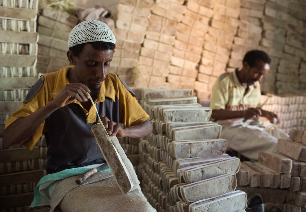 . Men prepare bars of salt to be sold in a shop in the main market of the city of Mekele, northern Ethiopia April 24, 2013. The Danakil Depression in Ethiopia is one of the hottest and harshest environments on earth, with an average annual temperature of 94 degrees Fahrenheit (34.4 Celsius). For centuries, merchants have travelled there with caravans of camels to collect salt from the surface of the vast desert basin. The mineral is extracted and shaped into slabs, then loaded onto the animals before being transported back across the desert so that it can be sold around the country. Picture taken April 24, 2013. REUTERS/Siegfried Modola