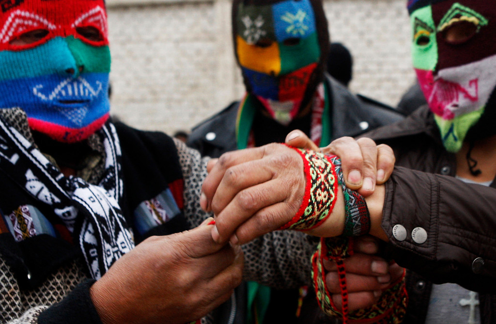 . Masked fighter Eber Sabina, right, gets help to wrap his hand before taking part in a Takanakuy ritual fight in Lima, Peru.  In Peru, it has long been practiced in the highlands province of Chumbivilcas near Cuzco. More recently, it has spread to outlying neighborhoods of Lima. (AP Photo/Karel Navarro)