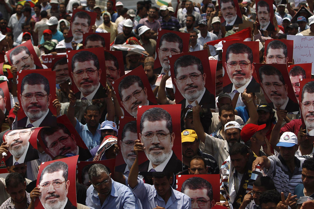 . Supporters of Egyptian President Mohamed Mursi hold up his posters during a rally to show support to him at the Raba El-Adwyia mosque square in Cairo July 3, 2013. At least 16 people were killed on Wednesday and 200 wounded when gunmen opened fire on supporters of Mursi who were rallying outside Cairo University, state television quoted a Health Ministry spokesman as saying. REUTERS/Khaled Abdullah