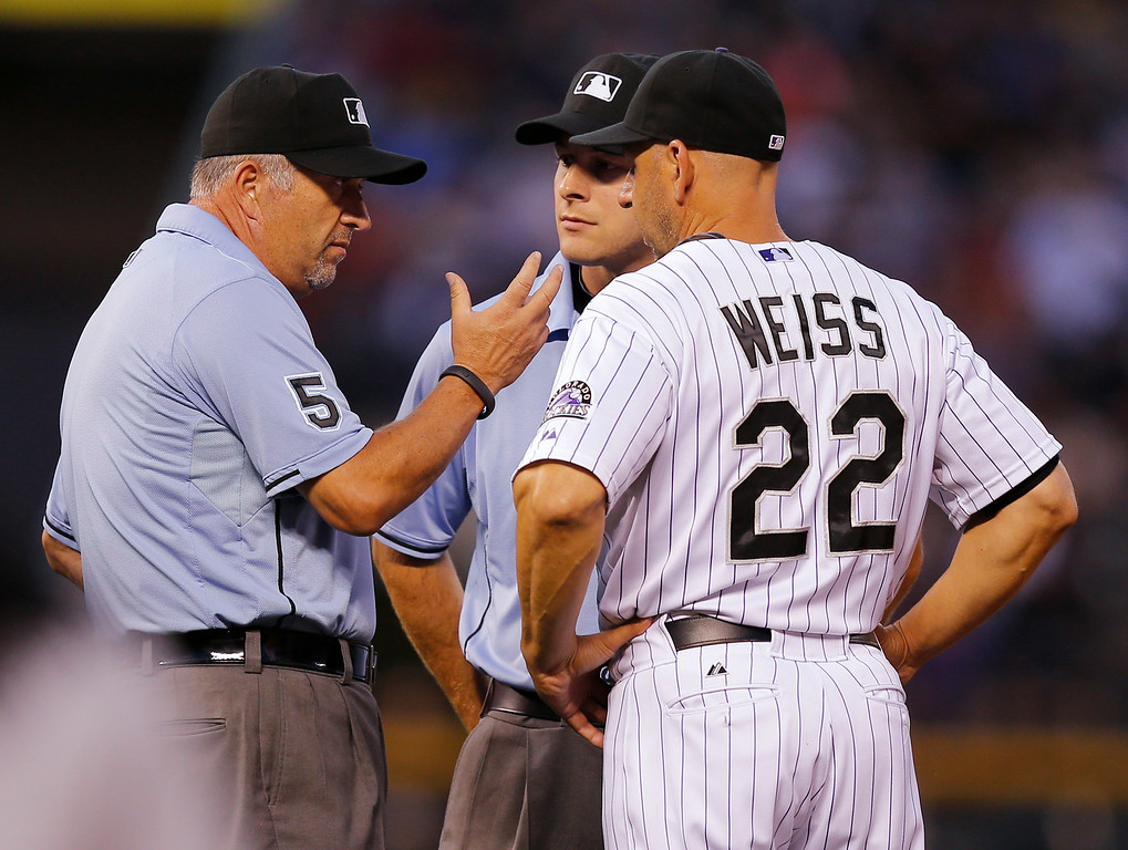 . Umpires Dale Scott, left, and Ben May talks to Colorado Rockies manager Walt Weiss after a play at second during the fourth inning of a baseball game against the Cincinnati Reds on Friday, Aug. 15, 2014, in Denver. (AP Photo/Jack Dempsey)