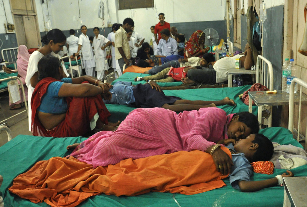. A parent (foreground) rests with her child at a ward housing Indian schoolchildren who consumed a free mid day meal at a school in the Saran district of Bihar state, at the Patna Medical College and Hospital in Patna on July 17, 2013.  Twenty-two children have died after eating a free lunch feared to contain poisonous chemicals at an Indian primary school, officials said, as the tragedy sparked angry street protests.  AFP PHOTOSTR/AFP/Getty Images