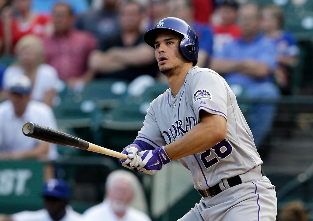 . Colorado Rockies\' Nolan Arenado watches the flight of his two-run double off a pitch from Texas Rangers\' Colby Lewis in the first inning of a baseball game, Wednesday, May 7, 2014, in Arlington, Texas. The hit, that extended Arenado\'s hitting streak to 27 games, scored Troy Tulowitzki and Carlos Gonzalez. (AP Photo/Tony Gutierrez)