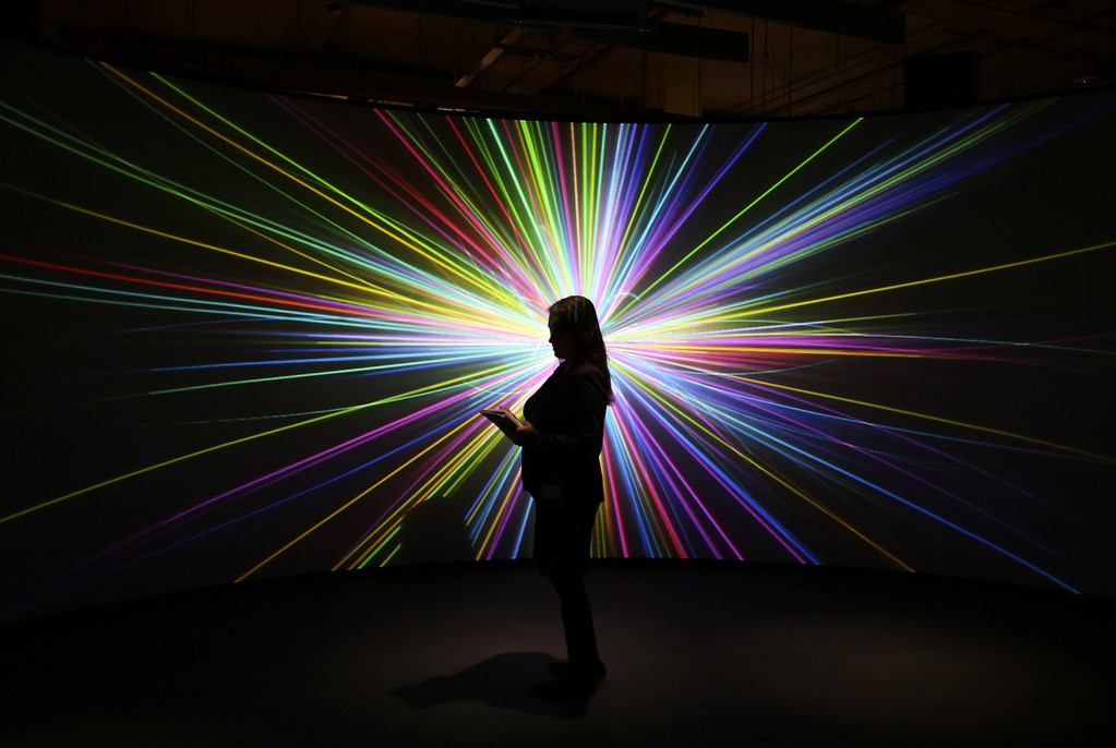 . An employee of the Science Museum stands in front of a video projection showing the workings of the Large Hadron Collider (LHC)  at the \'Collider\' exhibition on November 12, 2013 in London, England.  (Photo by Peter Macdiarmid/Getty Images)
