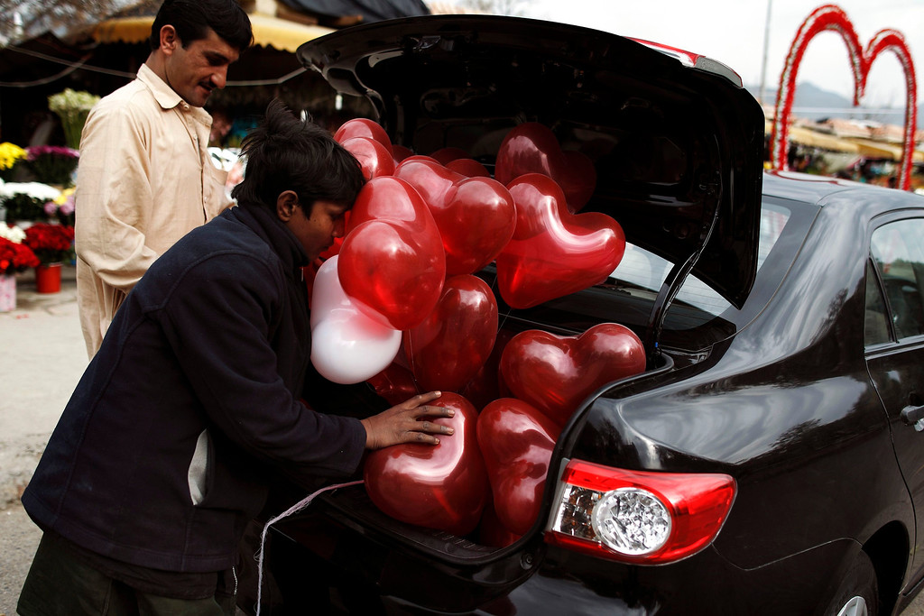 . A man tries to fit heart-shaped balloons in the trunk of his car on Valentine\'s Day in Islamabad February 14, 2013. REUTERS/Zohra Bensemra