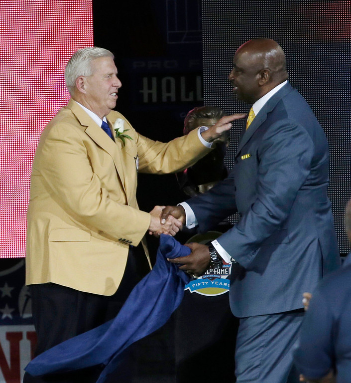 . Former NFL football head coach Bill Parcells, left, shakes hands with presenter George Martin during the induction ceremony at the Pro Football Hall of Fame Saturday, Aug. 3, 2013, in Canton, Ohio. (AP Photo/Tony Dejak)