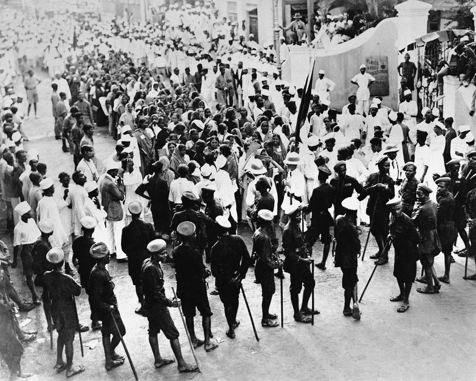 """. Police block an outlawed procession in front of the Nationalists\' Congress headquarters in Bombay, July 5, 1930, on the ground that it was in celebration of \""""defiance of authority\"""" in the Sholapur riots when fourteen people were killed. The native police, Mahratties, are shown in the foreground with their lathies or sticks of bamboo. Two European police sergeants, wearing helmets, are seen near the Gandhi flag. (AP Photo/J.P. Howe)"""