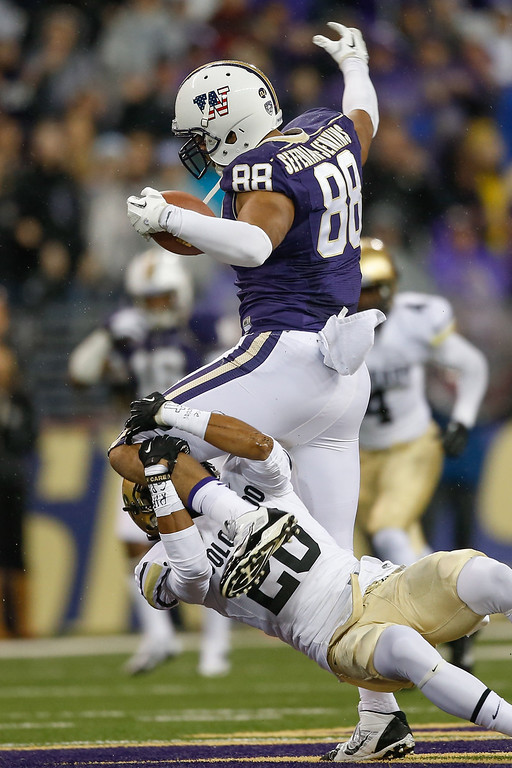 . Tight end Austin Seferian-Jenkins #88 of the Washington Huskies rushes against defensive back Ryan Severson #20 of the Colorado Buffaloes on November 9, 2013 at Husky Stadium in Seattle, Washington.  (Photo by Otto Greule Jr/Getty Images)