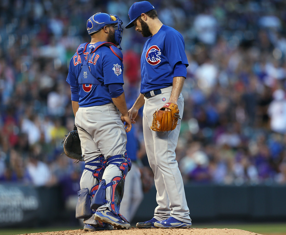 . Chicago Cubs catcher Wellington Castillo, left, confers with starting pitcher Jake Arrieta after Arrieta gave up an RBI single to Colorado Rockies\' Michael McKenry in the fourth inning of the Rockies\' 13-4 victory in a baseball game in Denver on Wednesday, Aug. 6, 2014. (AP Photo/David Zalubowski)