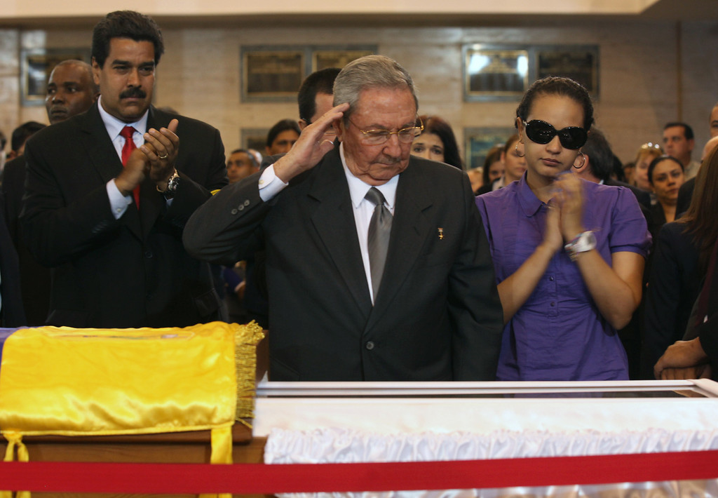 . Cuba\'s President Raul Castro salutes as he stands next to the coffin containing the remains of Venezuela\'s late President Hugo Chavez, during his wake at a military academy where his body will lie in state until his funeral, in Caracas, Venezuela, Thursday, March 7, 2013.  At right is Chavez\'s daughter Rosa Virginia Chavez and left is Vice-President Nicolas Maduro. (AP Photo/Miraflores Press Office)