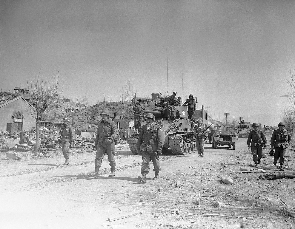 . First tanks and troops of the First Cavalry Division enter shell-scarred city of Chunchon after the last communist stronghold on central Korean front fell on March 21, 1951. Walking in center of road are (left to right): Maj. Gen. Charles D. Palmer, commanding the First Cavalry; and Col. Marcel G. Grombez, Portland, Ore., a regimental commander. (AP Photo/Jim Pringle