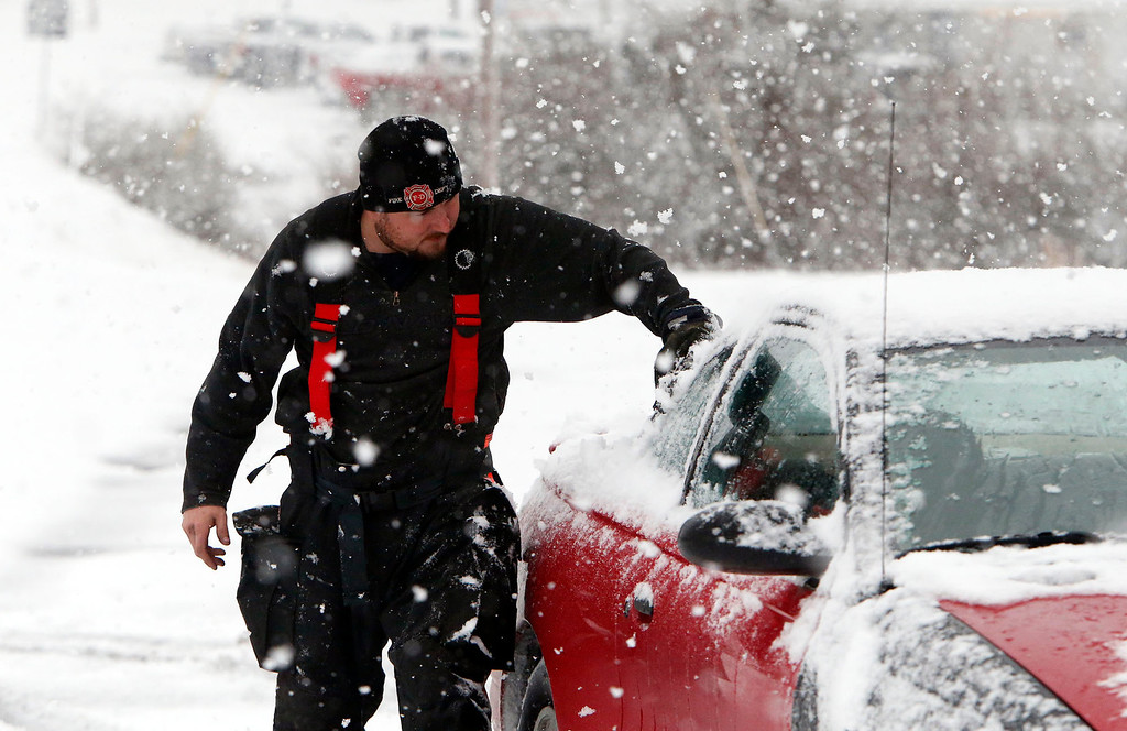 . Firefighter Robbie Hairell scrapes snow off of his car Tuesday Feb. 11,  2014 in Dog Town, Ala.  A winter storm dropped from 1 inch to 3 inches of wintry precipitation across a wide area, turning trees and roads white and forcing hundreds of schools, businesses and government offices to close or open late.  (AP Photo/Hal Yeager)