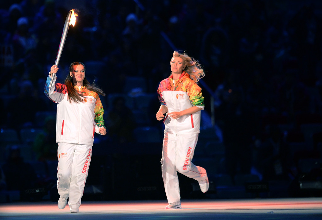 . Russian pole vaulter Yelena Isinbayeva, left,  runs with the Olympic torch next to Russian tennis player Maria Sharapova during the opening ceremony of the 2014 Winter Olympics, Friday, Feb. 7, 2014, in Sochi, Russia.  (AP Photo/Jung Yeon-je, Pool)