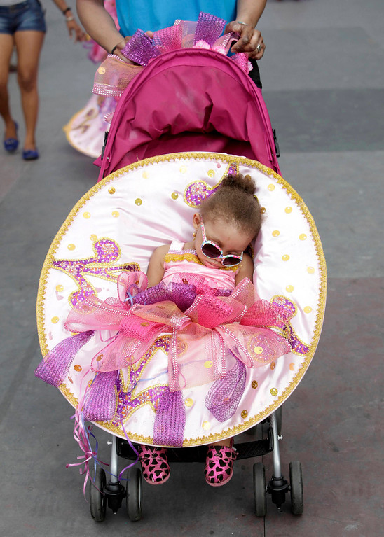 ". A girl from the children\'s carnival band ""Carnival Babies\"" sleeps while being pushed in a stroller at the Trinidad and Tobago Red Cross Society Children\'s Carnival at Queen\'s Park Savannah, Port of Spain February 2, 2013. REUTERS/Andrea de Silva"