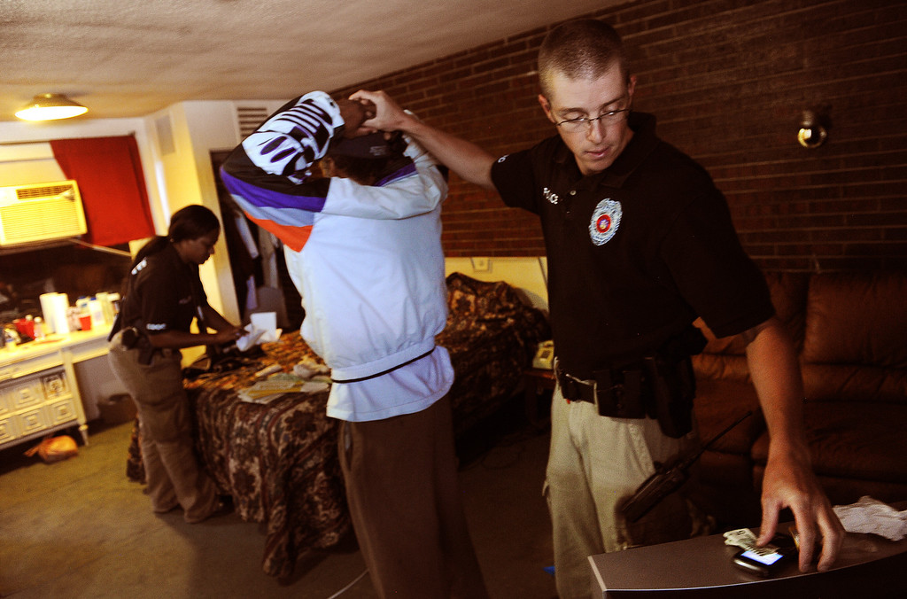 . ENGLEWOOD, CO - AUGUST 7:    Parole Officer Ryan Burch, right, gets ready to handcuff a parolee after a search of his room  at the Riviera Motel in Aurora, CO on August 7, 2013.  The parolee was arrested for violating parole when the officers found drug paraphernalia on his person.   Any kind of drugs, drug paraphernalia, pornography etc. are considered a violation of parole. The visits are unscheduled and the parolees never know when a parole officer is going to stop by their place of residence.  The officer is allowed to completely search their apartment looking for any parole violations.  The Riviera Motel is a place where many parolees go when they get out on parole.  They are given two weeks worth of vouchers to stay at hotels such as these along Colfax Ave.  (Photo by Helen H. Richardson/The Denver Post)