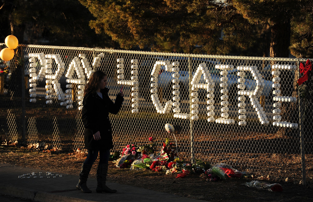 . Friends and students take a moment at a tribute to pray for shooting victim Claire Davis set up along Dry Creek road near Arapahoe High School in Centennial, CO on December 15, 2013. Students from the high school attended a prayer service to pray for the recovery of Davis who was shot during the recent shooting at the high school.  (Photo By Helen H. Richardson/ The Denver Post)