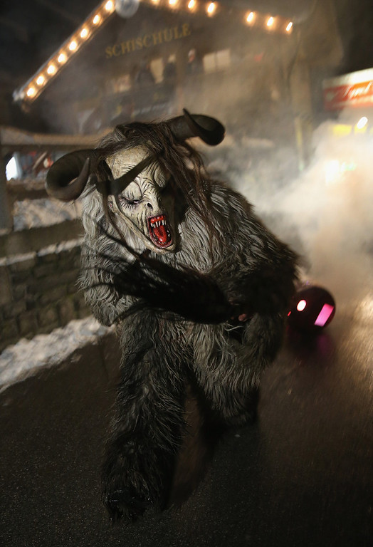 . A participant dressed as the Krampus creature pulls a barrel of fire during his search for delinquent children during Krampus night on November 30, 2013 in Neustift im Stubaital, Austria. Sixteen Krampus groups including over 200 Krampuses participated in the first annual Neustift event. Krampus, in Tyrol also called Tuifl, is a demon-like creature represented by a fearsome, hand-carved wooden mask with animal horns, a suit made from sheep or goat skin and large cow bells attached to the waist that the wearer rings by running or shaking his hips up and down. Krampus has been a part of Central European, alpine folklore going back at least a millennium, and since the 17th-century Krampus traditionally accompanies St. Nicholas and angels on the evening of December 5 to visit households to reward children that have been good while reprimanding those who have not. However, in the last few decades Tyrol in particular has seen the founding of numerous village Krampus associations with up to 100 members each and who parade without St. Nicholas at Krampus events throughout November and early December.  (Photo by Sean Gallup/Getty Images)