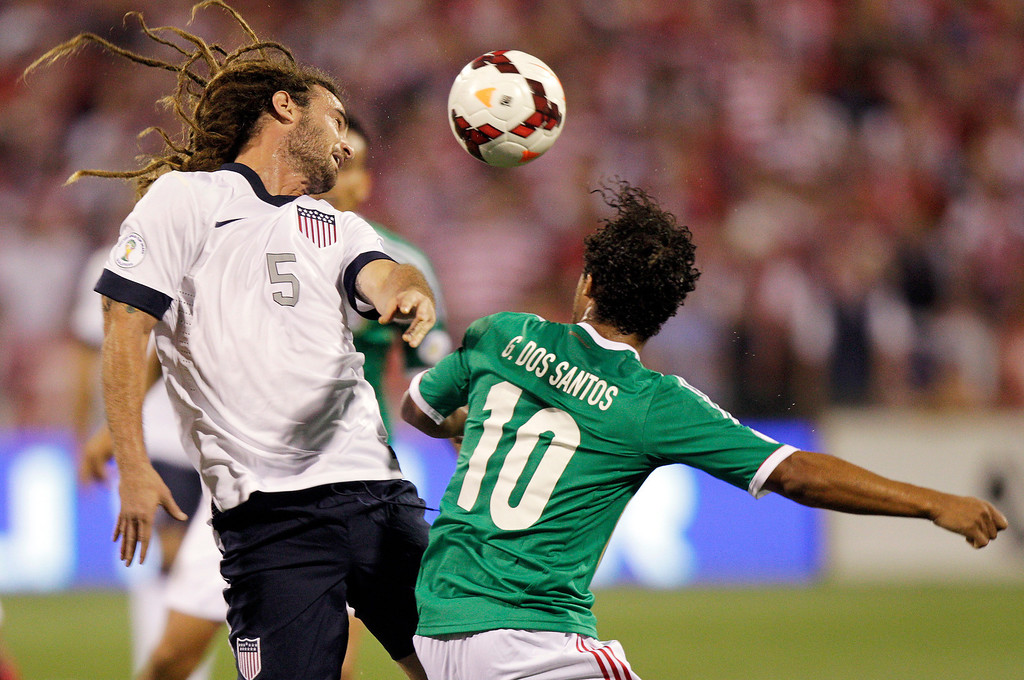. The United States\' Kyle Beckerman, left, heads the ball away from Mexico\'s Giovani dos Santos during the first half of a World Cup qualifying soccer match Tuesday, Sept. 10, 2013, in Columbus, Ohio. (AP Photo/Jay LaPrete)