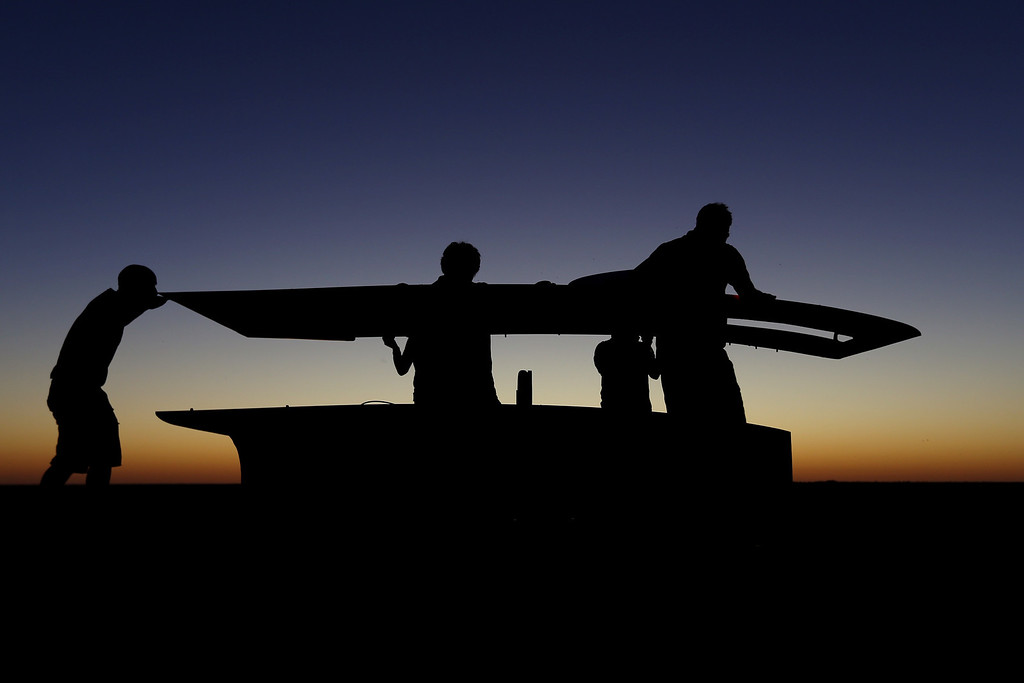 . ALICE SPRINGS, AUSTRALIA - OCTOBER 09:  The team of Arrow1 from Team Arrow, Associated with Queensland University of Technology in Australia position the car in the pre-dawn light to catch the sunrise light before racing on Day 4 on October 9, 2013 between Alice Springs and Kulgera, Australia. Over 25 teams from across the globe are competing in the 2013 World Solar Challenge - a 3000 km solar-powered vehicle race between Darwin and Adelaide. The race began on October 6th with the first car expected to cross the finish line on October 10th.  (Photo by Mark Kolbe/Getty Images)
