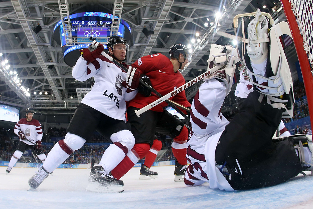 . Latvia\'s Georgijs Pujacs (L) vies for the puck with Switzerland\'s Nino Niederreiter during the Men\'s Ice Hockey Group C match between Latvia and Switzerland at the Sochi Winter Olympics on February 12, 2014 at the Shayba Arena.    Martin Rose/AFP/Getty Images