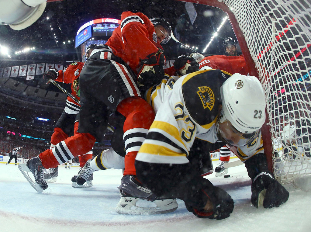 . Chicago Blackhawks\' Patrick Kane pushes Boston Bruins\' Chris Kelly into the net during the first period in Game 5 of their NHL Stanley Cup Finals hockey series in Chicago, Illinois, June 22, 2013. REUTERS/Bruce Bennett/Pool