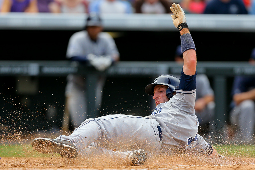 . DENVER, CO - JULY 9:  Chris Denorfia #13 of the San Diego Padres slides in to score during the fifth inning on a wild pitch by Jair Jurrjens (not pictured) of the Colorado Rockies at Coors Field on July 9, 2014 in Denver, Colorado. (Photo by Justin Edmonds/Getty Images)