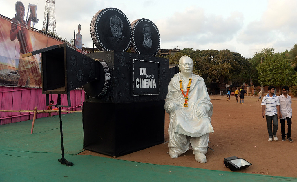". Patrons walk past a statue of Indian filmmaker Dadasaheb Phalke placed outside the Anup Touring Talkies tent cinema at a ground in central Mumbai on April 19, 2013.  To mark 100 years of Indian Cinema, a Marathi film ""Touring Talkies\"" is being screened in a makeshift tent theatre just like the days of yore, in its pre-multiplex and pre-single screen glory dating back 50 years. The tents, keeping in mind modern audiences, will have plush seating, air conditioning and popcorn and cola alongside fresh sugar-cane juice, roasted groundnuts and gram and pickle and other tit-bits. The cinema will screen four shows per day for a week. The idea of touring talkies was the brainchild of the doyne of Indian cinema, Dadasaheb Phalke, after he saw the British watching movies in tents. The touring cinema would travel through rural India and screen movies in makeshifts tents. At present, one can only find these talkies - whose sweltering tents and basic facilities contrast with the plush, air-conditioned multiplexes springing up in Indian cities, during Jatras (village fairs) in the interiors of the state.  INDRANIL MUKHERJEE/AFP/Getty Images"