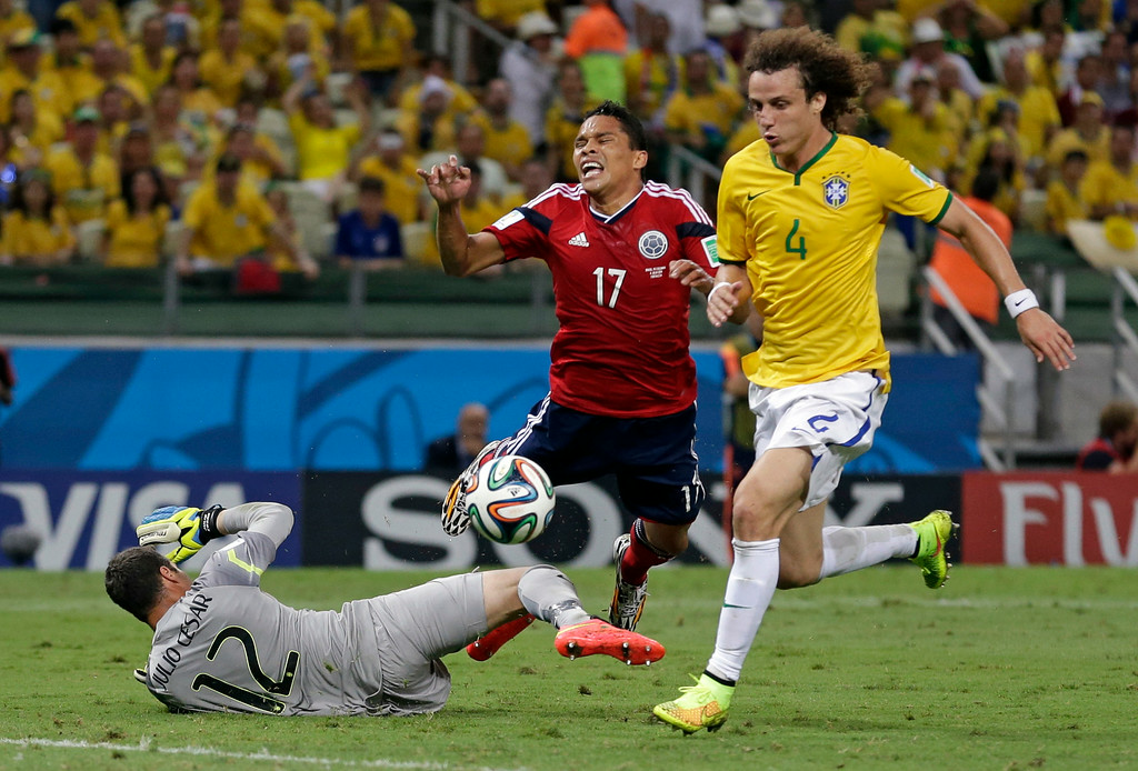 . Colombia\'s Carlos Bacca, center, is fouled by Brazil\'s goalkeeper Julio Cesar to give away a penalty during the World Cup quarterfinal soccer match between Brazil and Colombia at the Arena Castelao in Fortaleza, Brazil, Friday, July 4, 2014. (AP Photo/Felipe Dana)