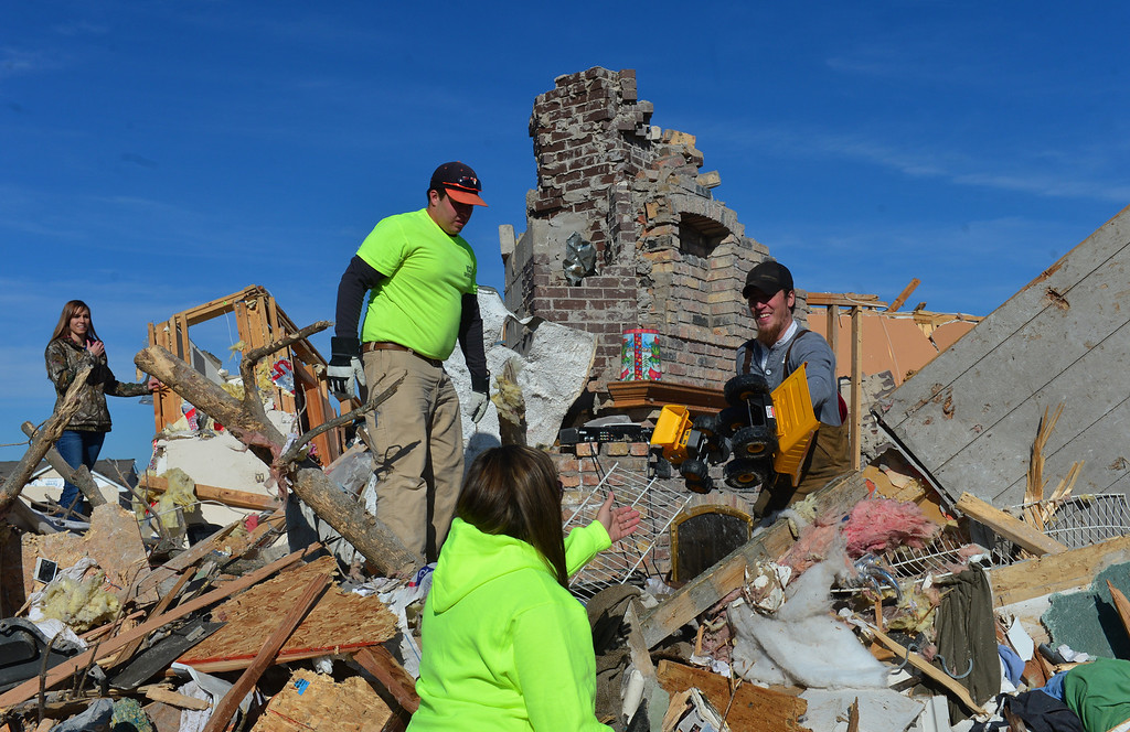 . Ryan Bernius, right, laughs as he recovers two two Caterpillar toys amid the rubble as homeowners dig out what they can Tuesday, Nov. 19, 2013, in Washington, Ill., after more than 1,000 homes were devastated by a F4 tornado that passed through Sunday. The twister was the most powerful to hit Illinois since 1885 with wind speeds greater than 200 mph. (AP Photo/Journal Star, Fred Zwicky)