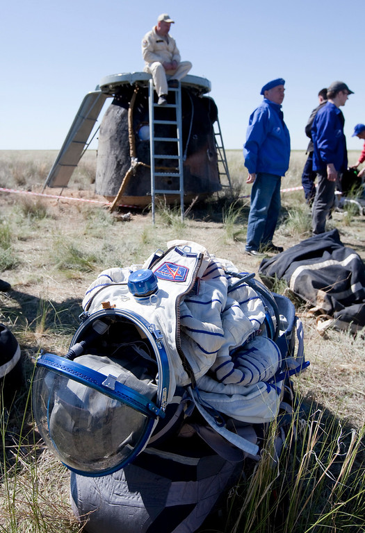 . A space suit is placed on the ground after the landing of the Russian Soyuz space capsule, seen in the background, some 150 km (90 miles) southeast of the town  of Dzhezkazgan in central Kazakhstan, Tuesday, May 14, 2013. (AP Photo/ Sergei Remezov, Pool)