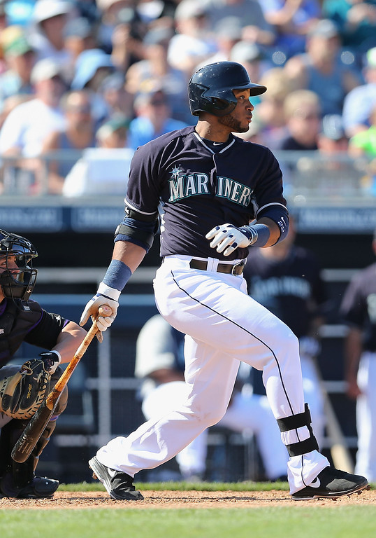 . Robinson Cano #22 of the Seattle Mariners hits a RBI single against the Colorado Rockies during the fifth inning of the spring training game at Peoria Stadium on March 3, 2014 in Peoria, Arizona.  (Photo by Christian Petersen/Getty Images)