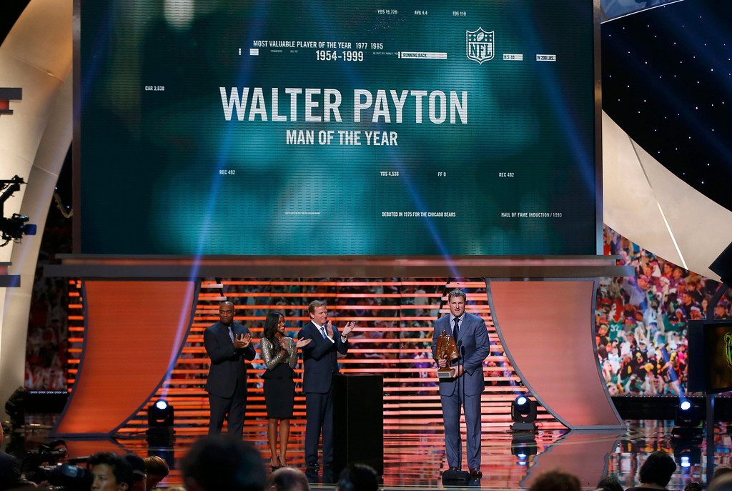 . Dallas Cowboys Jason Witten (R) holds the Walter Payton Man of the Year Award after it was presented to him during the NFL Honors award show in New Orleans, Louisiana February 2, 2013. From left are Payton\'s children, Jarrett and Brittney Payton and NFL Commissioner Roger Goodell.       REUTERS/Jeff Haynes