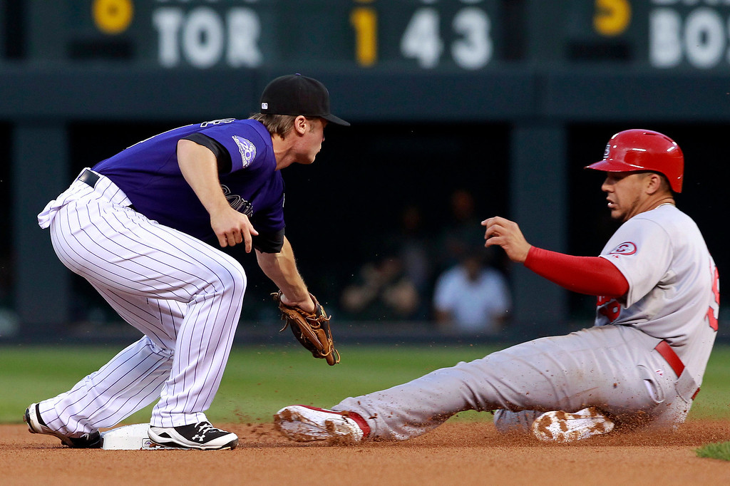 . Colorado Rockies second baseman Josh Rutledge, left, prepares to tag St. Louis Cardinals\' Jon Jay as he steals second base in the first inning of a baseball game in Denver on Tuesday, Sept. 17, 2013. (AP Photo/David Zalubowski)