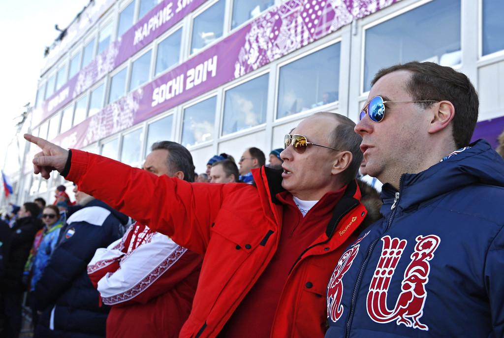 . Russian Prime Minister Dmitry Medvedev (R) and Russian President Vladimir Putin (L) watch the Men\'s 4x10 km Relay competition at the Sochi 2014 Olympic Games, Krasnaya Polyana, Russia, 16 February 2014.  EPA/DMITRY ASTAKHOV/RIA NOVOSTI/K