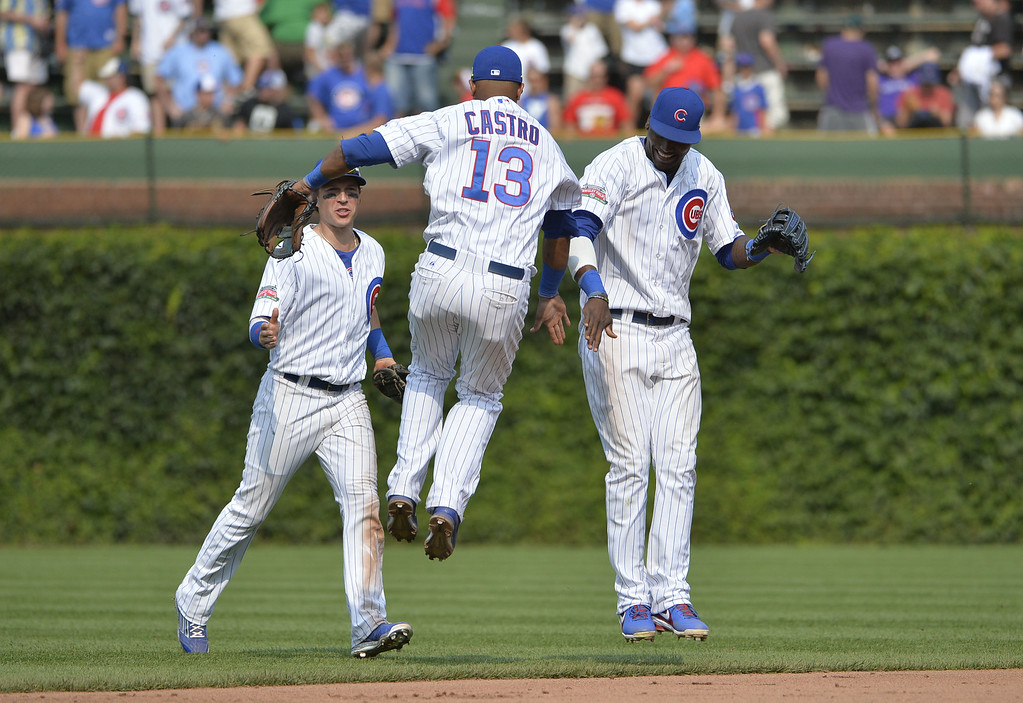 . Starlin Castro #13 of the Chicago Cubs and teammate Junior Lake #21 (R) celebrate their win over the Colorado Rockies at Wrigley Field on July 31, 2014 in Chicago, Illinois. The Cubs defeated the Rockies 3-1.  (Photo by Brian Kersey/Getty Images)