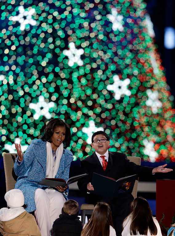 ". First lady Michelle Obama, left, and Rico Rodriguez, read ""The Night Before Christmas\"" to children during the 90th annual National Christmas Tree Lighting ceremony on the Ellipse south of the White House, Thursday, Dec. 6, 2012 in Washington. (AP Photo/Alex Brandon)"