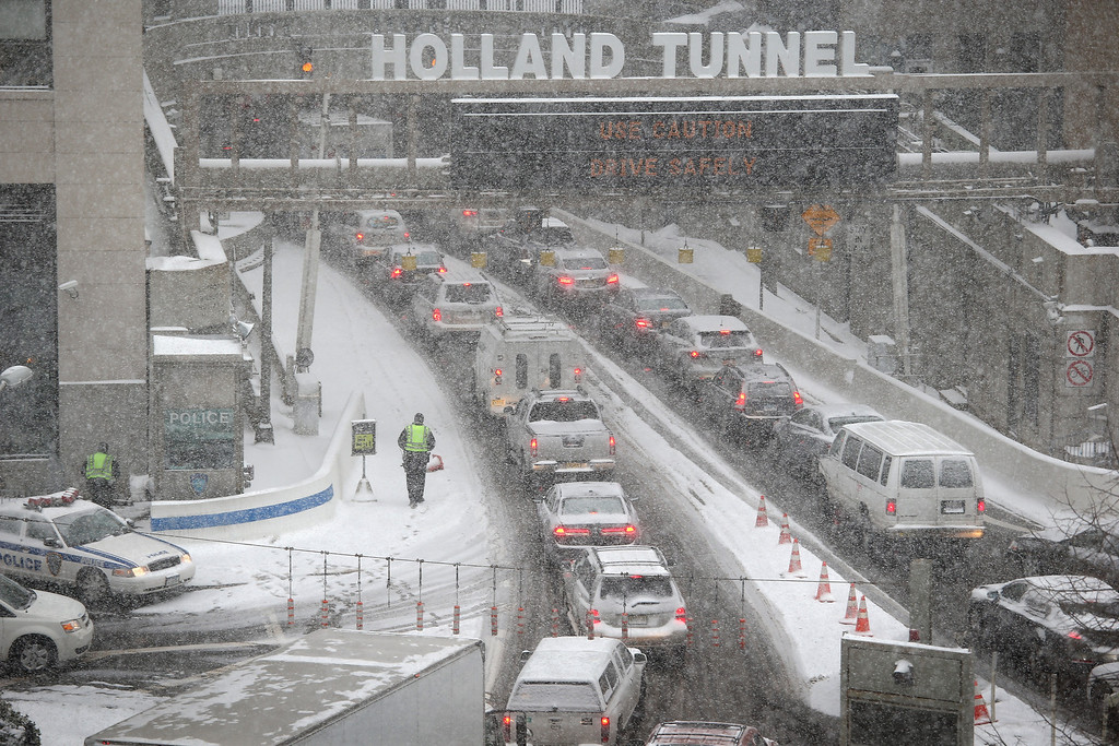. Traffic moves slowly through the snow into the Holland Tunnel from Manhattan during a snowstorm on January 21, 2014 in New York City. Areas of the Northeast are predicted to receive up to a foot of snow in what may be the biggest snowfall of the season so far.  (Photo by John Moore/Getty Images)